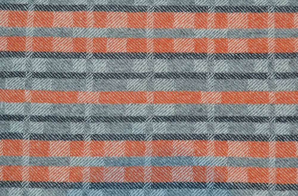 Handwoven 'Dukagang Stripe' lambswool throw in burnt orange and grey - showing reverse dominant colour side