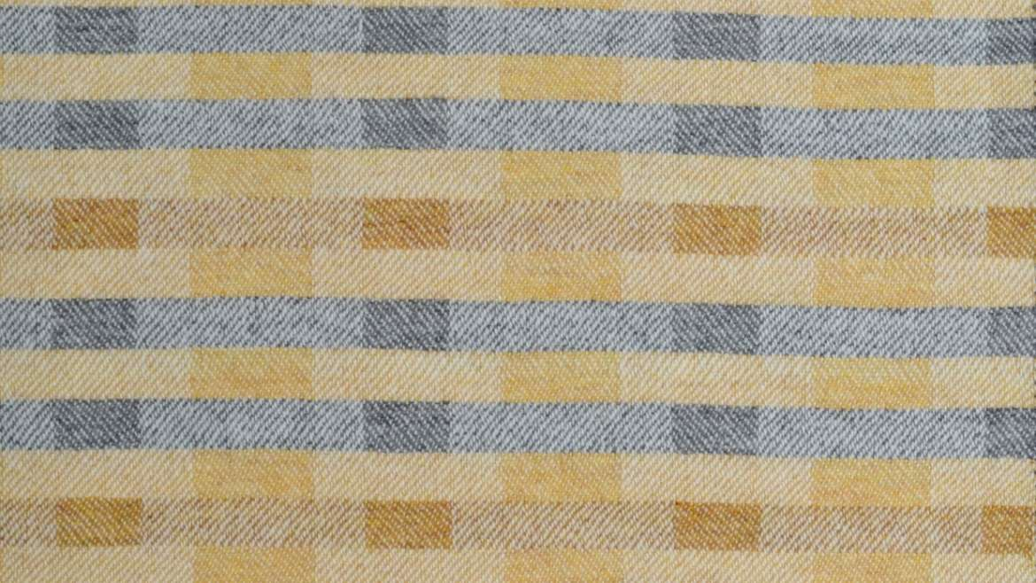 'Lineal' throw in soft ochre yellows and grey