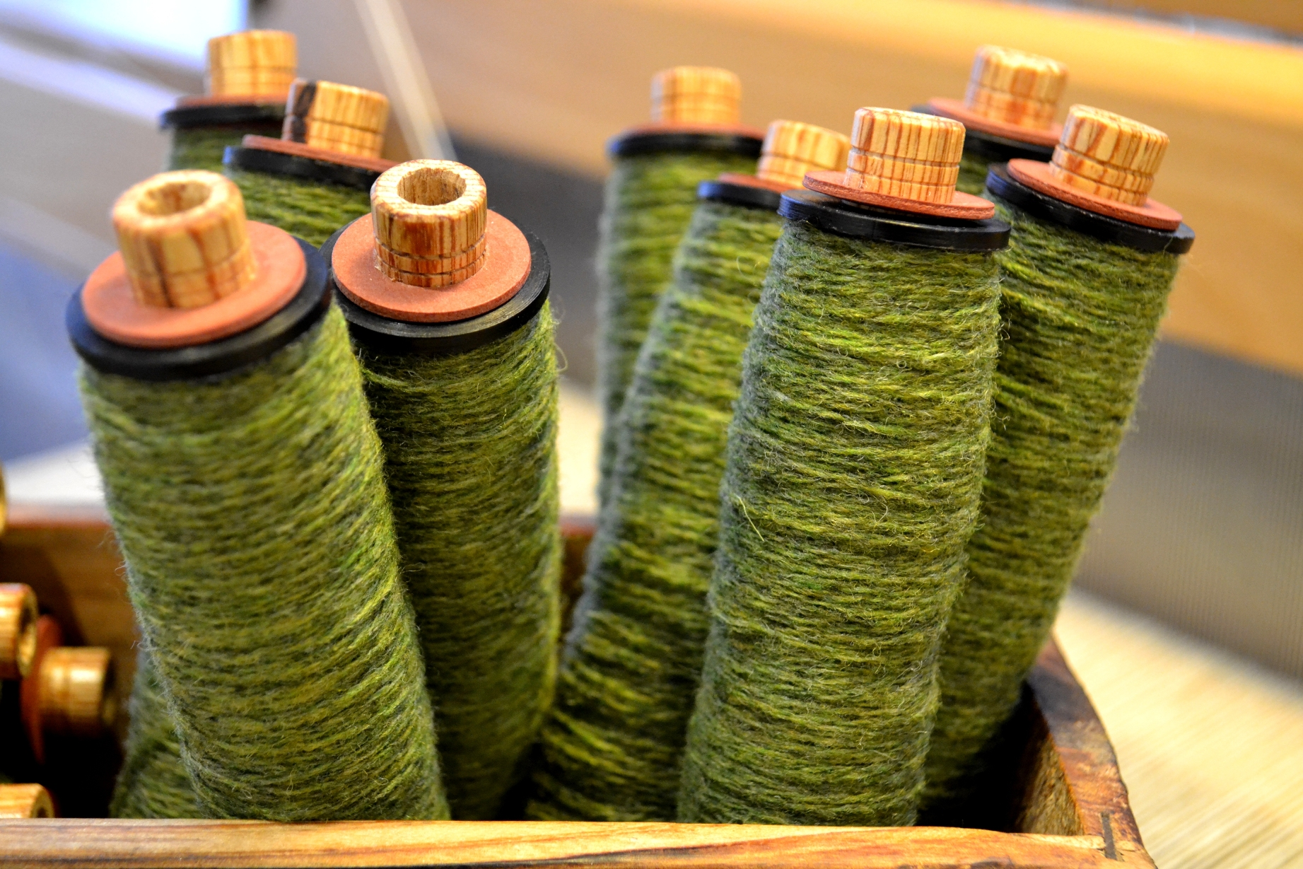 Green yarn on pirns ready for weaving