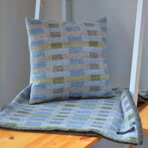 Handwoven 'Lineal' throw in blue, green and grey with cushion