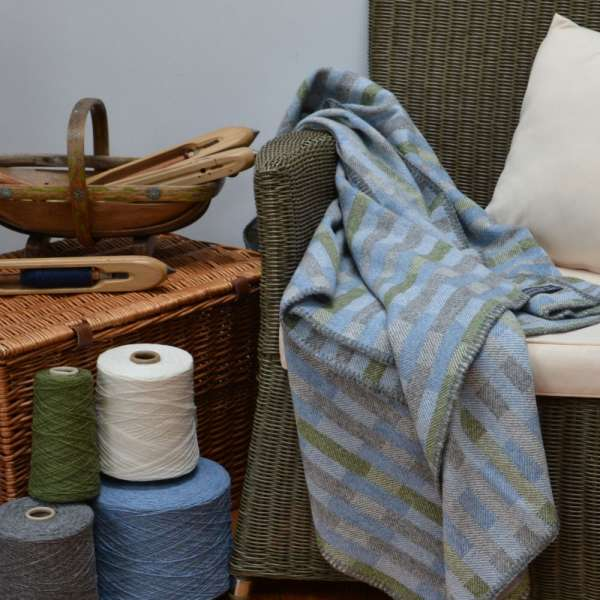 Handwoven 'Lineal' throw in blue, green and grey on chair